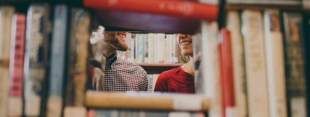 two people smiling at each other through a shelf of library books
