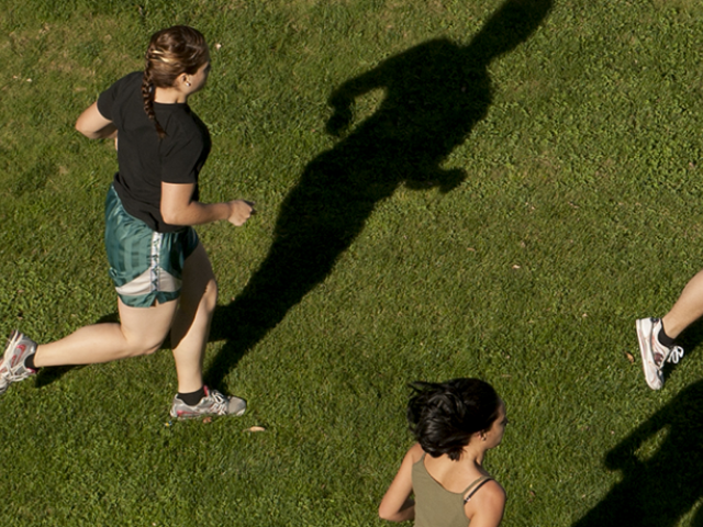 Group of people running through grassy green field