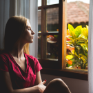 woman with closed eyes looking towards an open window