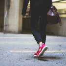 woman in red sneakers walking in an urban environment