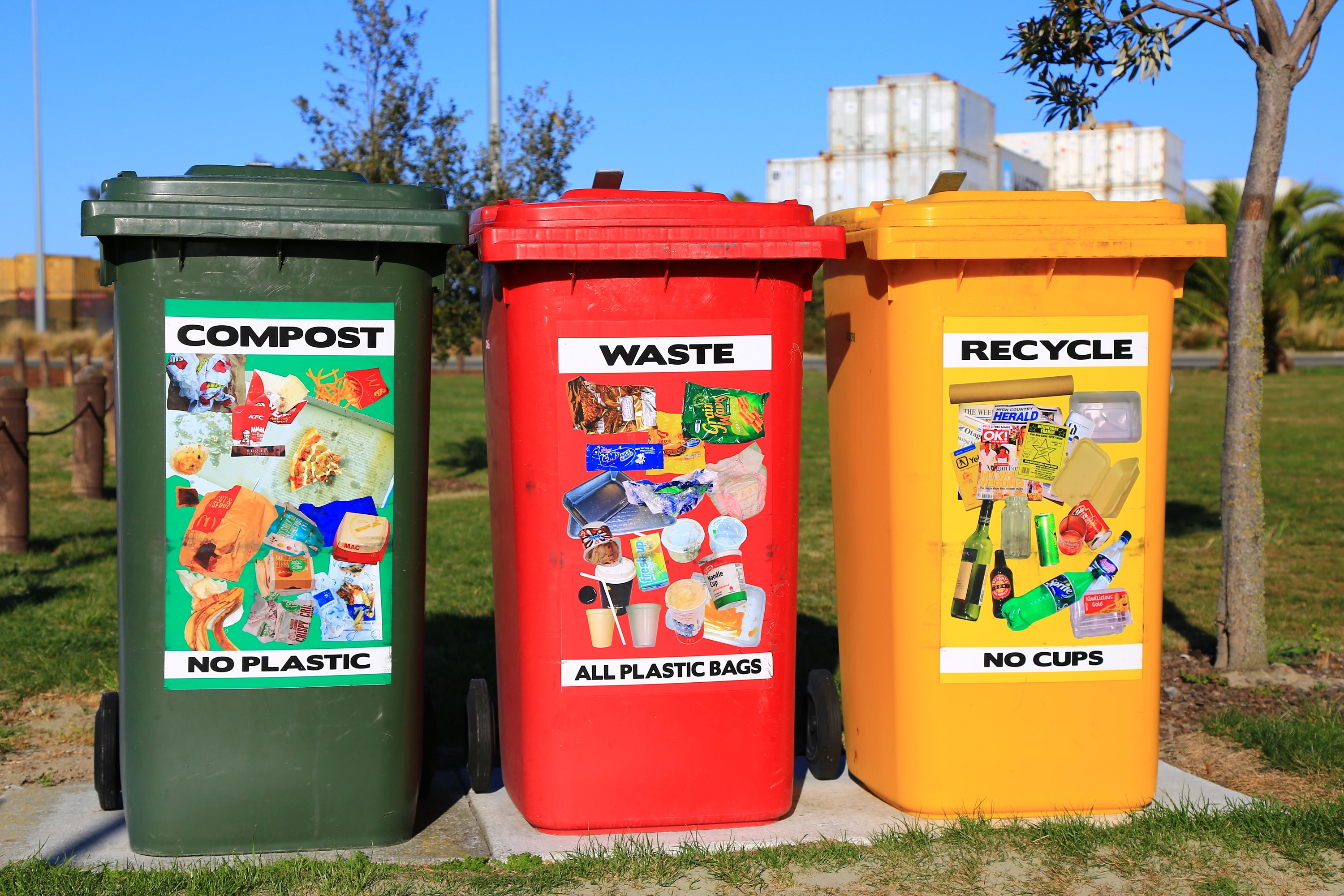 Three containers labeled for trash recycling and compost