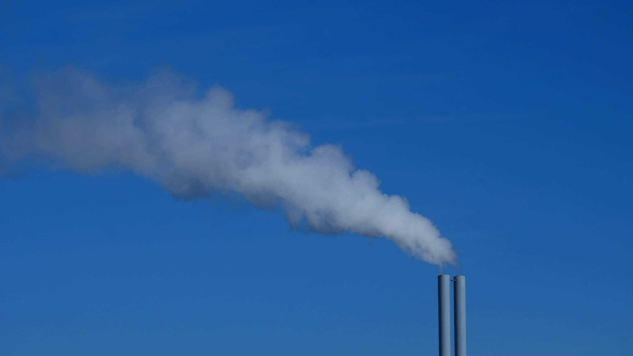 smoke stack in front of a blue sky with smoke blowing out