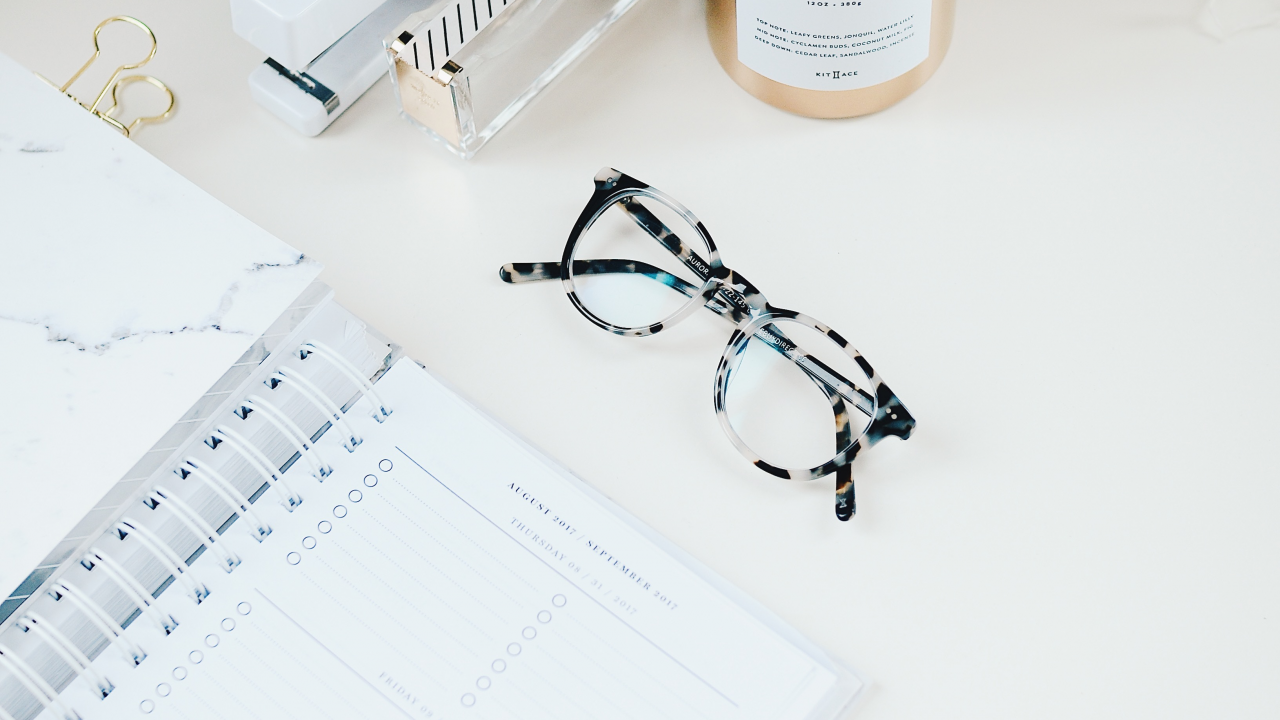 pair of glasses and diary sitting on a desk