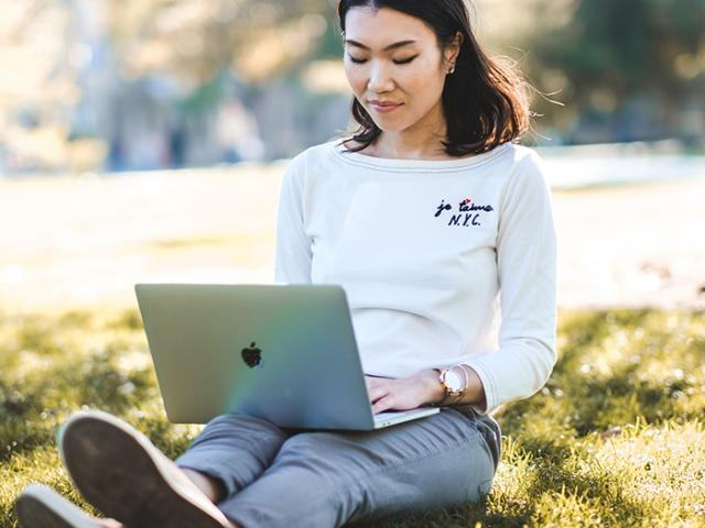 uc davis student using a laptop outdoors in the sun