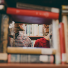 two people viewed with a stack of books