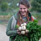 uc davis student farm worker with an armful of vegetables